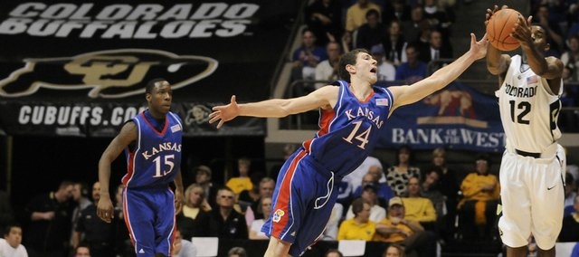Kansas guard Tyrel Reed lunges for a steal from Colorado guard Dwight Thorne II during the second half Saturday, Jan. 17, 2009 at the Coors Events Center in Boulder, Colorado. Left is Kansas guard Tyshawn Taylor.