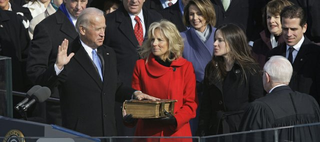Vice President-elect Joe Biden, with his wife Jill at his side, takes the oath of office from Justice John Paul Stevens, as his wife holds the Bible at the U.S. Capitol in Washington, Tuesday.