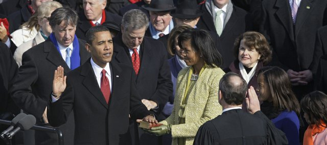 Barack Obama, left, joined by his wife Michelle, second from left, and daughters Sasha, third from left, and Malia, takes the oath of office from Chief Justice John Roberts to become the 44th president of the United States at the U.S. Capitol in Washington, Tuesday, Jan. 20, 2009.