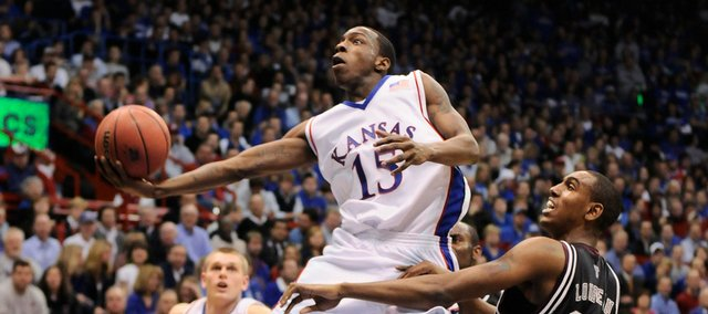 Kansas guard Tyshawn Taylor gets glides past Texas A&M forward David Loubeau for a bucket during the first half Monday, Jan. 19, 2009 at Allen Fieldhouse.
