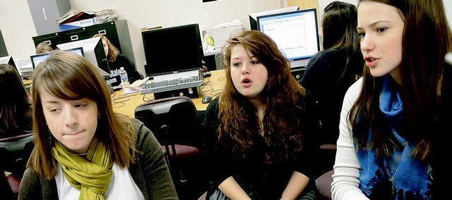 Erica Smith, left, a senior at Free State High School, works on designing layouts for the school's yearbook with her classmates Friday. Smith was paralyzed in a car accident in August 2008, and a run to benefit The Erica Smith Foundation is being organized for March. Working with Smith are seniors Kelly Kelin, center, and Apollonia Shreders.