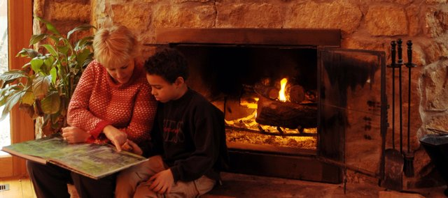 Ann Cooper reads with her son, Jimmy, in their old sandstone farmhouse in central Lawrence. Ann and her husband, James Cooper, have been renovating the property, which was nearly hidden by juniper trees.