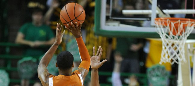 Texas guard A.J. Abrams (3) shoots over Baylor's Kevin Rogers (23) during the second half of an NCAA college basketball game Tuesday, in Waco, Texas. Abrams scored 19 points while matching the Big 12 career record for 3-pointers as No. 11 Texas won 78-72.
