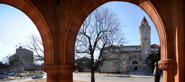 Viewed through the front arches of Spooner Hall is Dyche Hall, right of center, one of several historical buildings on the Kansas University campus. At left, in the distance, is Danforth Chapel and Fraser Hall. A new pilot purchasing program has the potential to help universities save time and money.