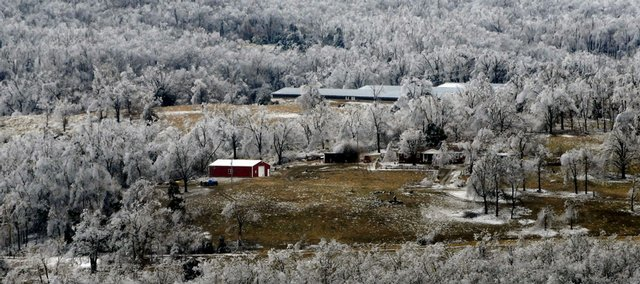 An aerial view of a home near Harrison, Ark., is surrounded by ice-covered trees Friday. Thousands of people are waiting to have their electricity restored after a powerful ice storm this week took down electrical wires and telephone poles across the north Arkansas landscape.