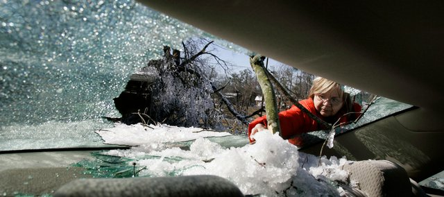 Gail Hatchett picks snow, ice and glass out of the back of her car after a tree limb smashed her back window during a recent ice storm Saturday in Draffenville, Ky. The storm left thousands in the area, including Hatchett, without power.