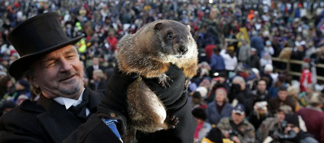 John Griffiths, a handler of the weather-predicting groundhog Punxsutawney Phil, holds Phil in the air after removing him from his stump at Gobbler's Knob on Groundhog Day, Monday, Feb. 2, 2009, in Punxsutawney, Pa. The Groundhog Club said Phil saw his shadow and predicted six more weeks of winter.