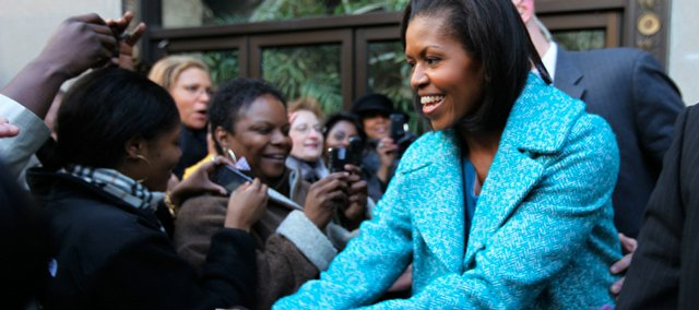 First lady Michelle Obama stops to shakes hands with a crowd that gathered last week outside Georgia Brown's Restaurant, near the White House in Washington.