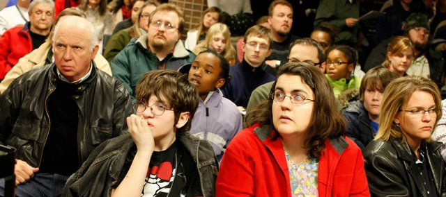 An overflow crowd watches the proceedings of the city commission hearing on budget cuts on a closed circuit television.