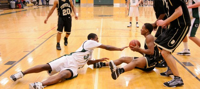 Eric Watson, on floor at left, goes for loose ball for Free State in the Firebirds' game against Topeka High Tuesday at Free State High.