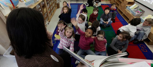 Students in Connie Levin's kindergarten class raise their hands to answer questions during story time Wednesday at Daniel Warren Elementary School in Mamaronek, N.Y. Throughout the year Levin has incorporated famous figures from different cultural backgrounds, including African-American history, to teach her students a universal concept of mutual respect and a sense of community.