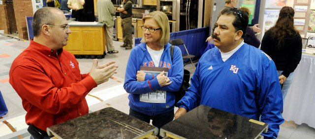 From left, Jeff Wyatt, Paradise Carpet One, talks with Mary and Bruce Lopez, Lawrence, at Saturday's Home Show at First Serve Tennis Center, 5200 Clinton Parkway.