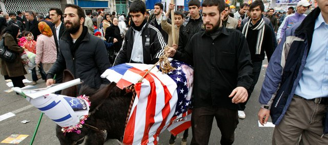 Iranian men lead a donkey draped in a representation of a US flag, and a hat representing an Israeli flag, in a rally Tuesday commemorating the 30th anniversary of the 1979 Islamic revolution that toppled the late U.S.-backed Shah Mohammad Reza Pahlavi, at the Azadi Square in Tehran, Iran.