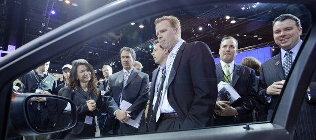 A crowd looks at the 2010 Ford Taurus SHO on display at the Chicago Auto Show Wednesday. The government has proposed tax deductions paid on the purchase of a new passenger car, minivan or light-duty truck this year in its federal stimulus bill passed by the Senate on Tuesday.