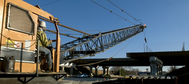 A construction worker moves a crane toward the site of a new Kansas Turnpike bridge extending over North Third Street.