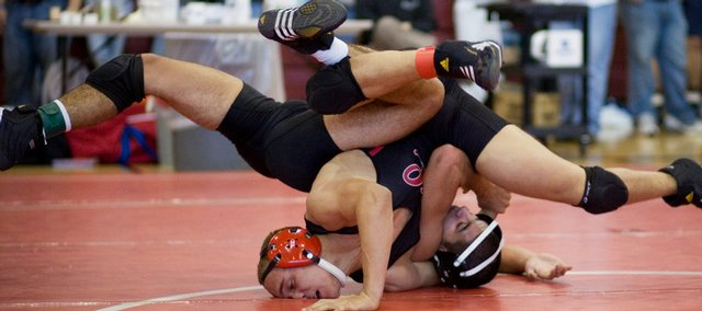 Lawrence High wrestler Reece Wright-Conklin, in red headgear, competes during the Sunflower League championships. Wright-Conklin won the league title at 152 pounds on Saturday at Shawnee Mission North.