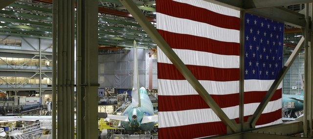 "A U.S. flag hangs above the Boeing 747 line at Boeing Co.'s airplane assembly plant in Everett, Wash. Today, ""Made in USA"" is more likely to be stamped on airplanes, silicon chips, medical equipment and other goods bought by companies than on TVs, toys, clothes and items you'd find on store shelves."