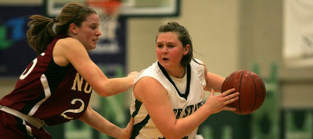 Free State senior Lexi Smith looks for an open teammate while being covered by Shawnee Mission North's Susan Specht during Tuesday night's game in Lawrence. The Indians defeated the Firebirds 45-36.