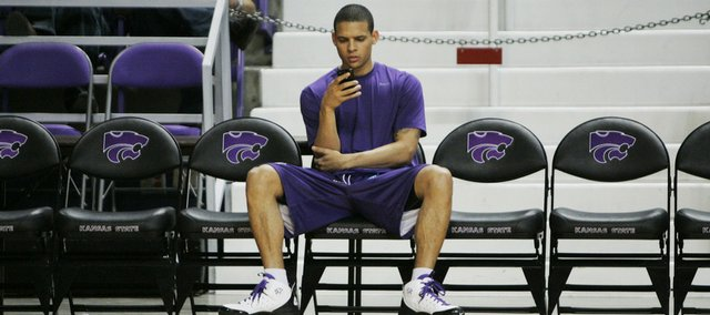 Kansas State guard Denis Clemente sits on the bench while his team warms up for their game against North Carolina Central in Manhattan, Kan., Tuesday, Feb. 17, 2009.