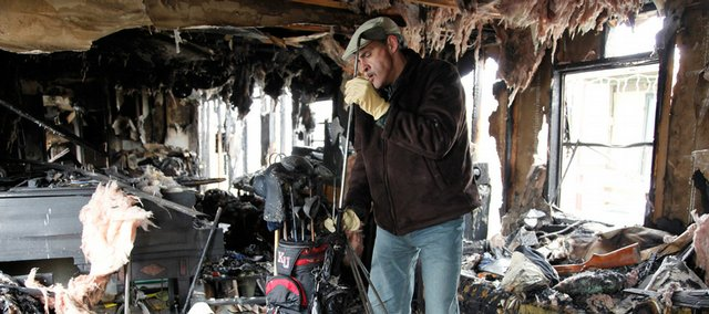 Lawrence resident Ben Allen discovers on Wednesday that his golf clubs survived a fire that destroyed his mobile home. His piano, at left, and most of his other belongings were a total loss in the Feb. 13 blaze at 1908 E. 19th St. He did not have insurance.
