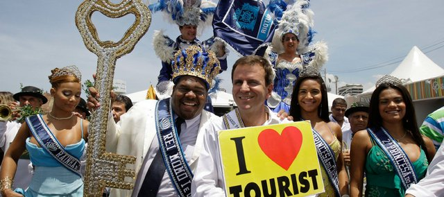 The Rei Momo, or Carnival King, second left, holds the key of the city of Rio de Janeiro as Mayor Eduardo Paes holds a sign after a ceremony marking the official start of Carnival celebrations Friday in Rio de Janeiro.
