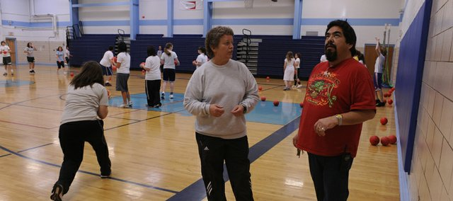 Julie Miller chats with James Ortiz, head custodian at West Junior High School, during a recent physical education class she was supervising. This is Ortiz's first year as head custodian.