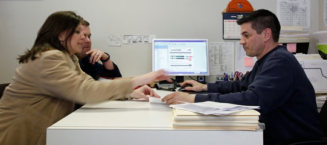 Jamie and Adam Gabriel consult with Jerrad Humerickhouse in preparing their income tax forms. The Hume's Econotax office has seen many changes in the way people are filing their taxes due to the recession and increasing unemployment.