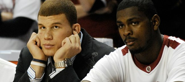 Sidelined with a concussion, Oklahoma forward Blake Griffin plugs his ears from the crowd noise as he sits next to center Orlando Allen during the first half at the Lloyd Noble Center in Norman, Okla.
