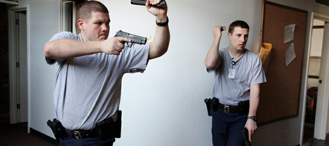 Lawrence Police Department recruits Samuel Hiatt, left, and Christopher Hatfield go through training exercises Monday at the former fire station at Stone Barn Terrace and Lawrence Avenue. The recruits — 12 men and one woman in all — are halfway through the academy. They'll get their badges on April 10 and will spend 14 weeks in field training before taking to the streets alone.
