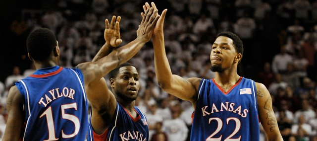 Kansas players Tyshawn Taylor, Sherron Collins and Marcus Morris come together for a collective high five after a bucket in the first half at the Lloyd Noble Center in Norman, Okla.