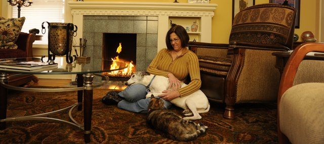 Jennifer Lutz relaxes in her Old West Lawrence home with cat Friday and dog Buddy. Lutz has been renovating the house since buying it in 1989. She has discovered a deed to the house that dates back to the 1860s.