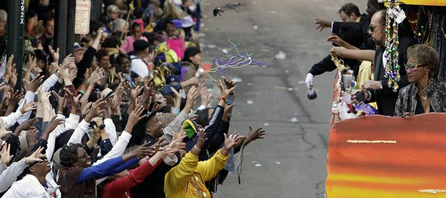 People reach for Mardi Gras beads thrown from a float in the Zulu parade Tuesday as it winds its way through the streets of the central business district in New Orleans. Seven bystanders were shot Tuesday after the last parade.