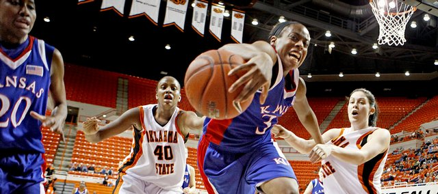 Kansas University's Porscha Weddington chases the ball between Oklahoma State's Shyvon Spears (40) and Tegan Cunningham. The Jayhawks beat the Cowgirls, 67-52, Wednesday in Stillwater, Okla.