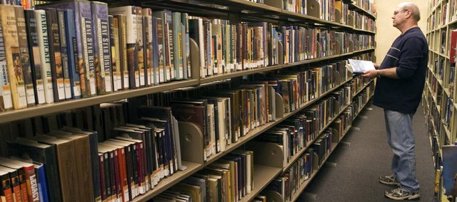 Len Hanson, of Lawrence, browses the shelves Wednesday at the Lawrence Public Library, 707 Vt. The library r