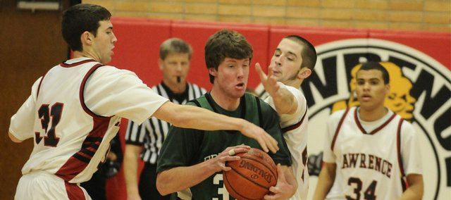 Lawrence High senior forwards Lance Kilburn, left, and Paul Eltschinger look to trap Free State junior center Michael Swank during the first half of the city showdown Friday, Feb. 27, 2009 at Lawrence High. In back is Lawrence High senior guard Robbie Wright.