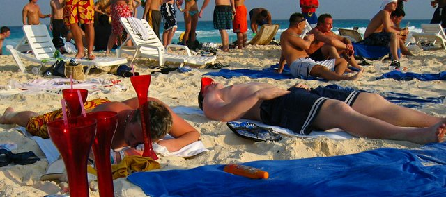 In this Monday March 17, 2003 file photo, students from the United Sates on spring break sunbathe at Cancun beach, Mexico. The U.S. State Department and universities around the country are warning college students headed for Mexico for some spring-break partying of a surge in drug-related murder and mayhem south of the border.