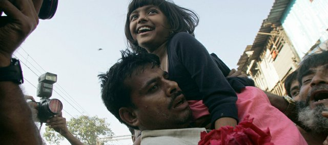 """Slumdog Millionaire"" child actor Rubina Ali, 9, reacts as she is welcomed back Thursday on her return to her home at a slum in Bandra, in suburban Mumbai, India. The child stars of the Oscar-winning ""Slumdog Millionaire"" returned to India on Thursday to a chaotic but rousing heroes' welcome. ""Slumdog Millionaire,"" a tale of hope amid adversity set in Mumbai, was awarded eight Academy Awards, including best picture and best director for Britain's Danny Boyle."
