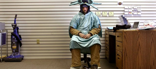 "Kurt Wilson, of Fenton, Mo., who works four hours a day waving in a Statue of Liberty costume for Liberty Tax, takes a break at the Brentwood, Mo., office. Wilson's wife didn't want him to take the job. ""She thought it was beneath me,"" he said."