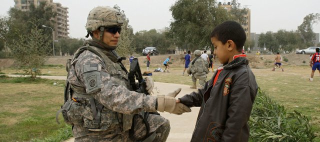 A U.S. soldier shakes hands with an Iraqi child during a routine patrol Friday in central Baghdad, Iraq. U.S. President Barack Obama will announce Friday that he plans to withdraw the bulk of U.S. troops from Iraq by the end of August 2010, but wants to leave tens of thousands behind to advise Iraqi forces and protect U.S. interests, congressional officials said.