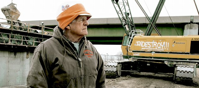 Ron Tucker, of Topeka, supervises a construction crew pouring concrete Friday for the bridge project over the Kansas River. Tucker has been working on bridge construction crews for 40 years.