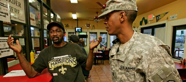 Louisiana National Guard Lt. Ronald Brown, Jr., RIGHT, talks with businessman Calvin Stewart on Thursday at Stewart's restaurant in the Ninth Ward of New Orleans. The last units of the Louisiana National Guard, which came to town after Hurricane Katrina in August of 2005, are pulling out Sunday.