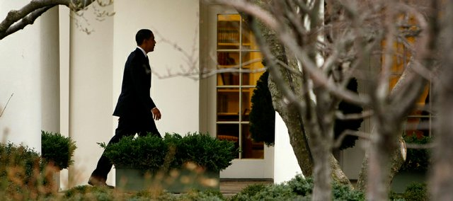 President Barack Obama walks to the Oval Office on Friday after arriving on the South Lawn of the White House in Washington.