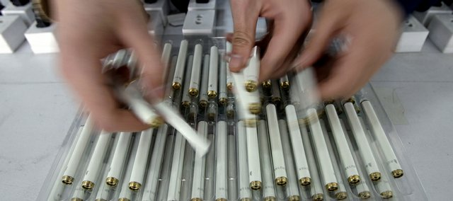 Workers place partially assembled electronic cigarettes in a tray  Feb. 19 at the Ruyan factory in Tianjin, China.The battery-powered products, which resemble real cigarettes but produce a fine nicotine spray absorbed quickly and directly by the lungs, are gaining ground in America, Europe and China, which is home to 350 million smokers.