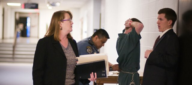 Douglas County chief assistant district attorney Amy McGowan talks with defense attorney Kevin Babbit as his defendant is shackled outside the Division IV courtroom following the afternoon docket, Wednesday at the Law Enforcement Center.