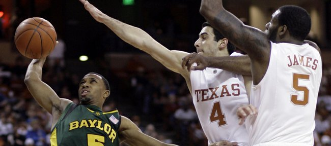 Baylor guard Henry Dugat, left, tries to shoot against the defense of Texas guards Dogus Balbay, center, and Damion James. The Longhorns won, 73-57, Monday in Austin, Texas.