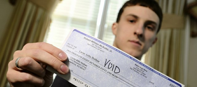 "Kansas University freshman Luke Hothan, Ozawkie, displays a fake check he received before taking part in what he believed to be a ""mystery shopper scam."" Before Hothan attempted to deposit the check, he did some investigating and found that the bank account the check was drawn on did not exist."