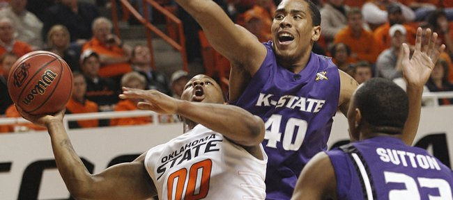 Oklahoma State guard Byron Eaton, left, takes a shot in front of Kansas State forwards Ron Anderson, center, and Dominique Sutton during the first half in Stillwater, Okla., Tuesday, March 3, 2009. Eaton scored 25 points in his final regular-season home game to lead Oklahoma State to a 77-71 win.