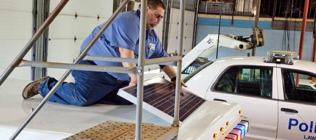 Terry Eaton installs a new solar panel on a Lawrence city ambulance. The solar panel will allow the ambulance's electronic systems to receive power without the engine running, reducing fuel consumption and emissions.