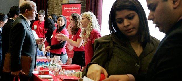 A couple, right, reads through the list of attending employers as they stand near one of the recruiting tables during the New Jersey Diversity Career Day job fair at Rutgers University on Feb. 20 in New Brunswick, N.J. In the current economic meltdown, virtually no group of workers is immune from unemployment.