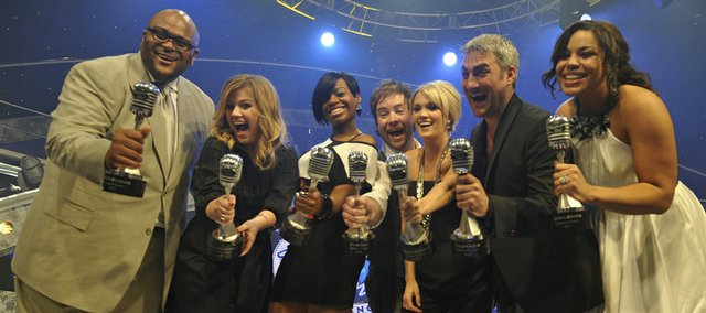 "the seven winners of ""American Idol,"" from left, Ruben Studdard, Kelly Clarkson, Fantasia Barrino, David Cook, Carrie Underwood, Taylor Hicks and Jordin Sparks  hold silver microphone awards as they pose for the grand opening of The American Idol Experience attraction at Walt Disney World Resort on Feb. 12 in Lake Buena Vista, Fla."